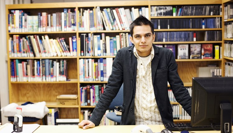 Young man leaning on table in library