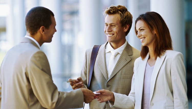 close-up of two businessmen and a businesswoman exchanging business cards
