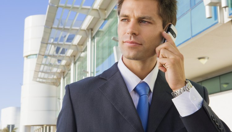 Businessman listening to cell phone outdoors