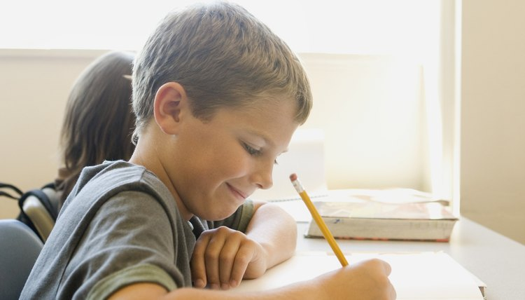 Smiling young student writing at desk.
