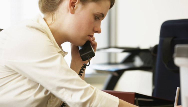 Side profile of a businesswoman using a telephone in an office