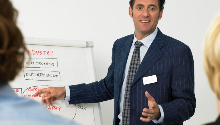 Businessman giving presentation, pointing to flipchart, smiling