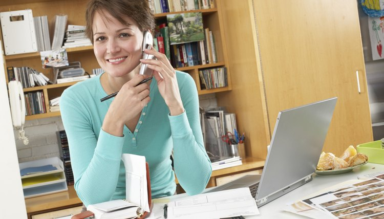 Woman using mobile phone, in home office, smiling, portrait