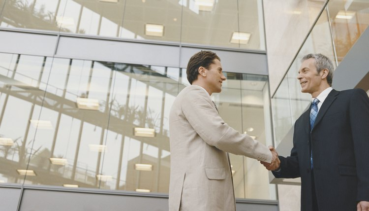 Two Businessmen Shaking Hands Standing Outside an Office Building