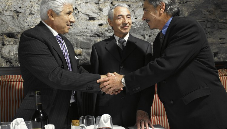 Three businessman greeting each other in restaurant, smiling