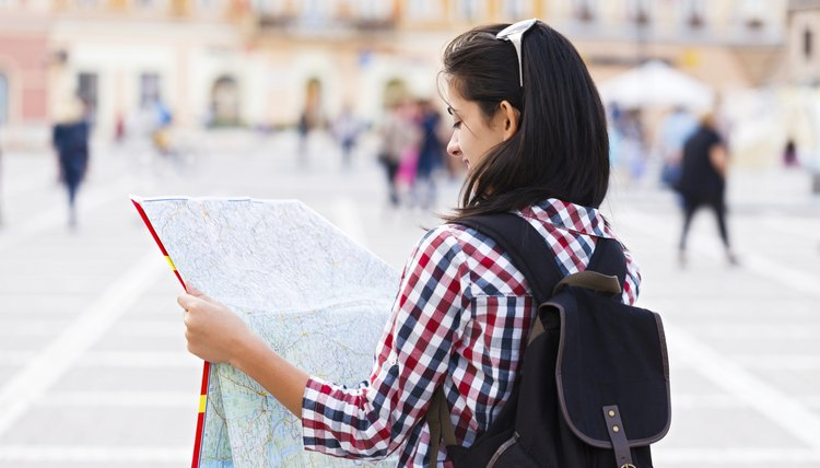 Student holding map up in foreign country