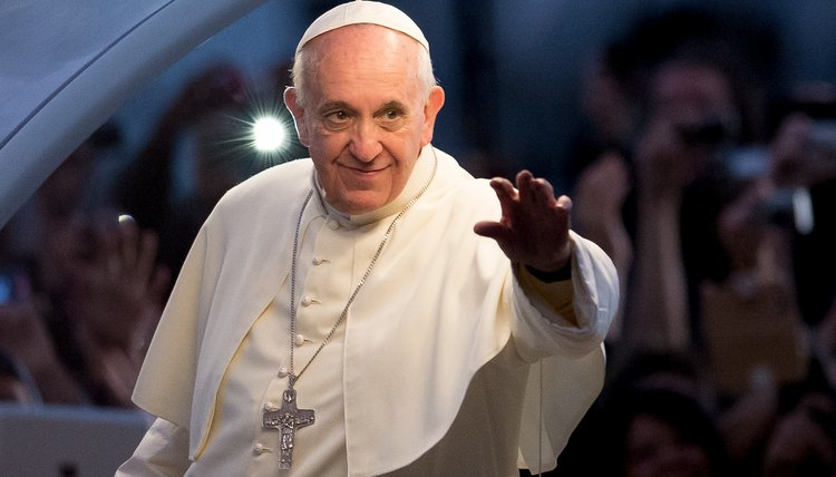 A pope greets a crowd of people.