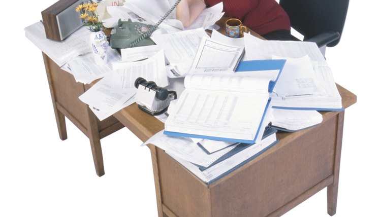Businesswoman using telephone at cluttered desk