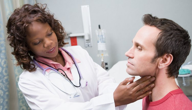 Doctor examining glands of throat of patient
