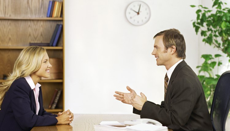 side profile of a businesswoman and a businessman talking to each other