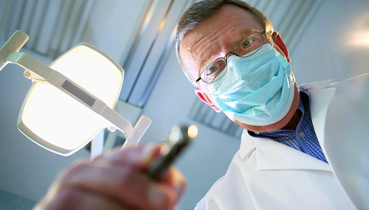 Point of view from the dental chair as a dentist leans over the viewer with a drill and the light above him