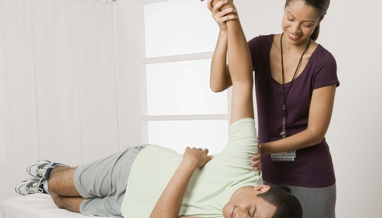 Physical therapist stretching arm of patient