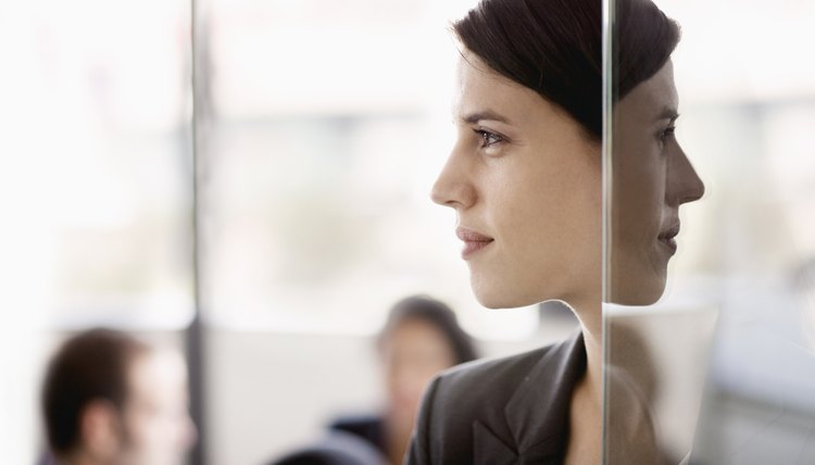 Side profile on a businesswoman with coworkers in the background