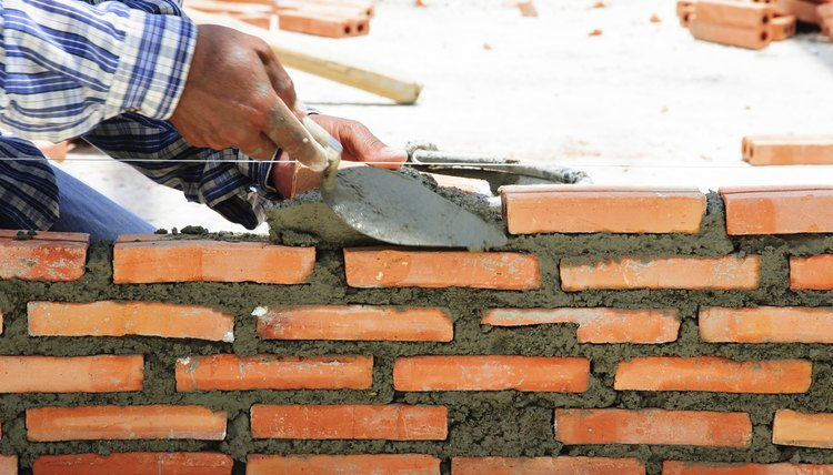 construction mason worker bricklayer installing brick with trowe