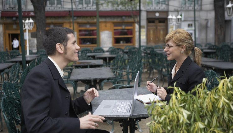 Side profile of two business executives sitting in an outdoor cafe