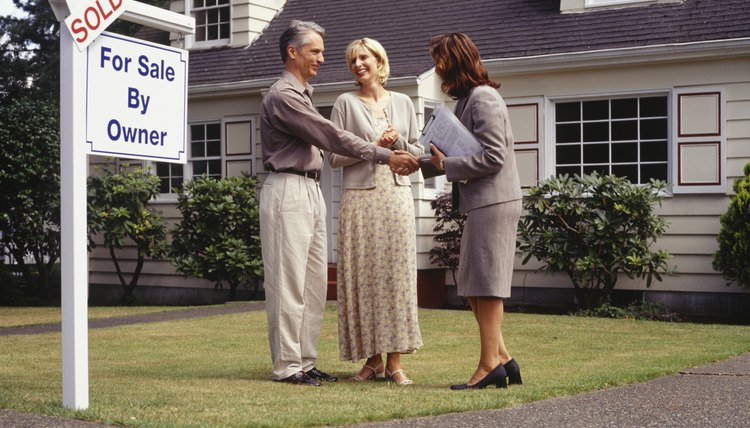 Real estate agent shaking hands with man on front lawn of sold house