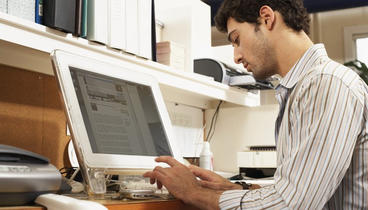 Male office worker sitting at workstation, typing