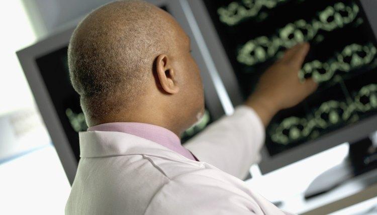 Radiologist pointing at MRI monitor screens
