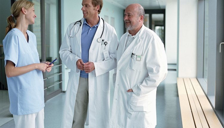 Female nurse talking with two mature male doctors in hospital corridor