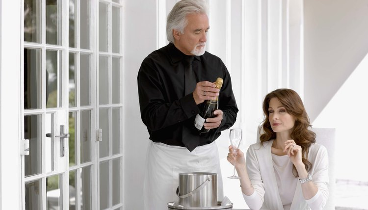 Butler serving woman champagne
