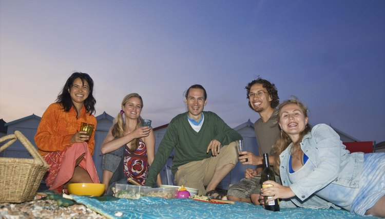 Reconnect with friends at an evening picnic on the beach.