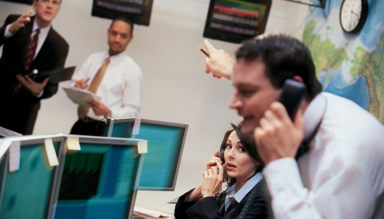 Stock brokers in office on phones