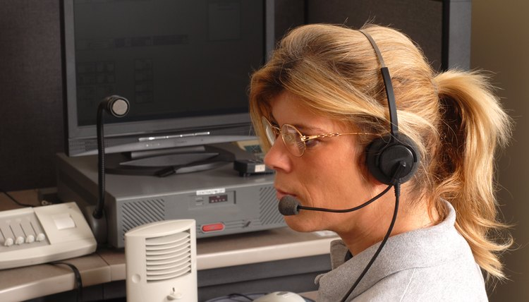 A dispatcher wearing a headset taking a call at a desk.