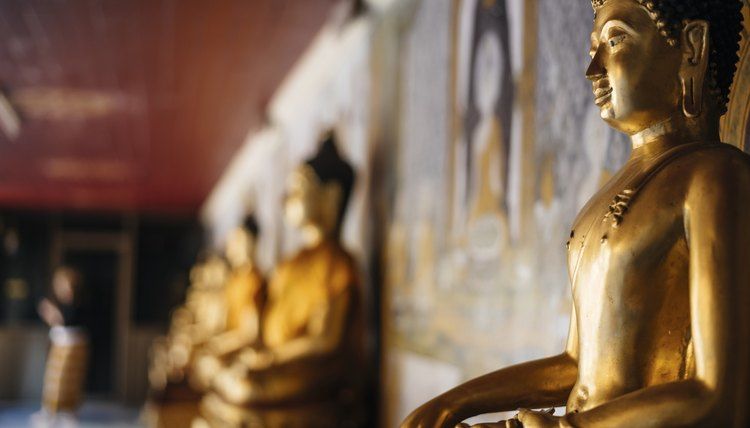 A row of golden Buddha statues inside of a temple.