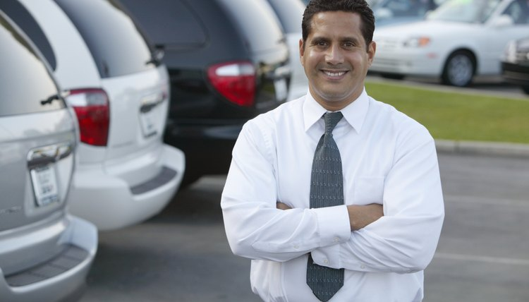Car salesman standing in car lot, arms folded, smiling, portrait