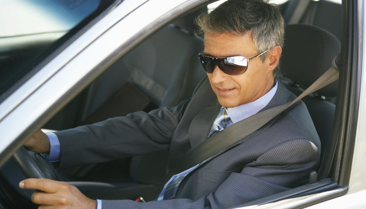 Businessman wearing shades in car, close up, elevated view
