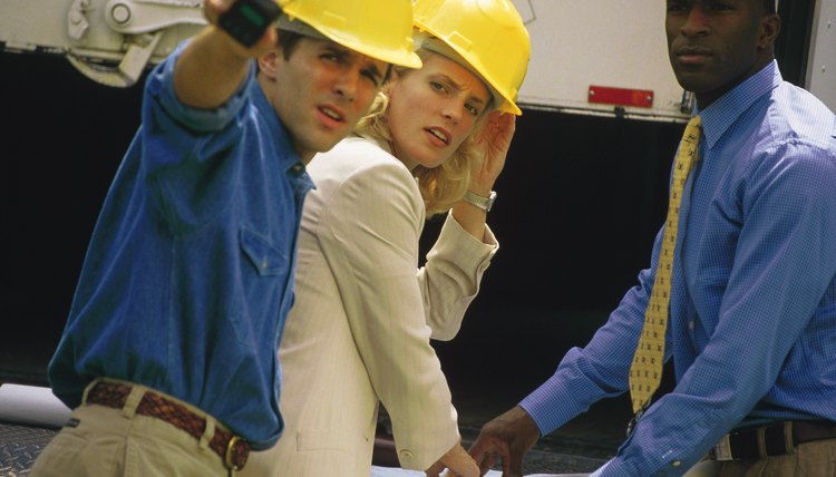 Group of people reviewing blueprints at construction site