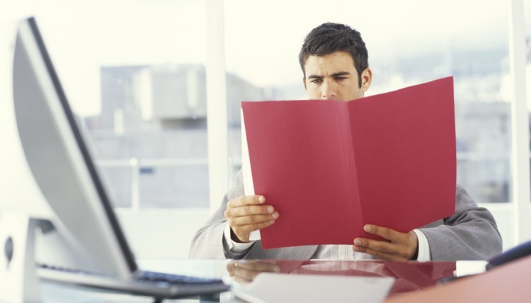Young businessman at desk looking at folder