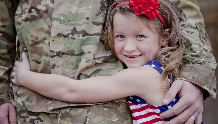 Little girl hugging soldier