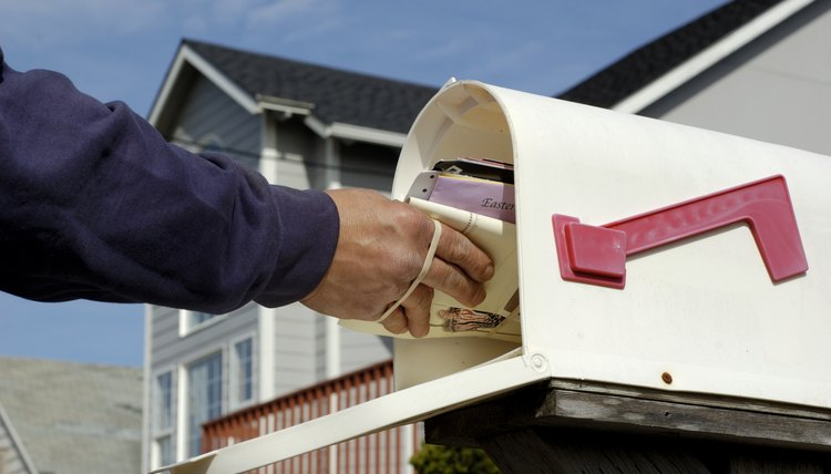 Postal worker delivering mail to a letterbox.