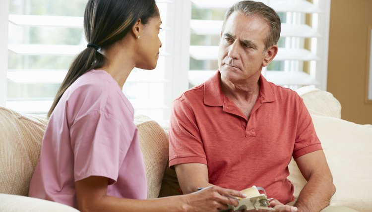 Nurse Discussing Records With Senior Male Patient During Home Vi