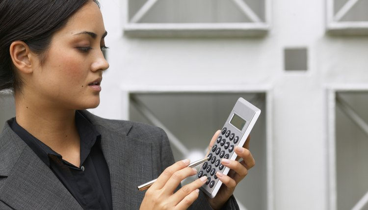 side view of a businesswoman holding a calculator and a pen
