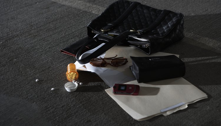 Purse and scattered items on ground in parking garage, elevated view