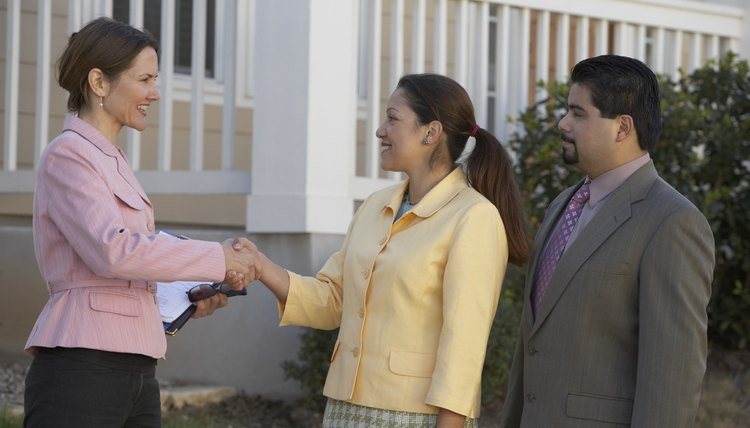 Portrait of a mature couple shaking hands with a real-estate agent
