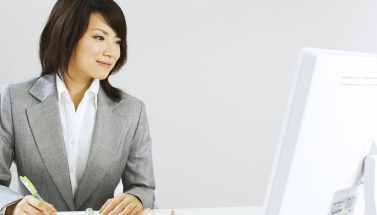A business woman is sitting at her desk taking notes.