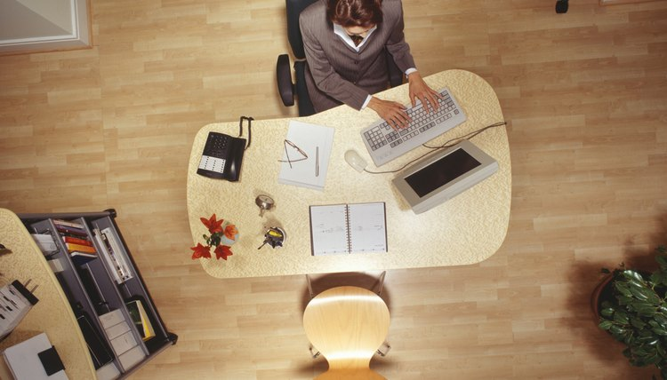 Businesswoman working on computer in office, overhead view