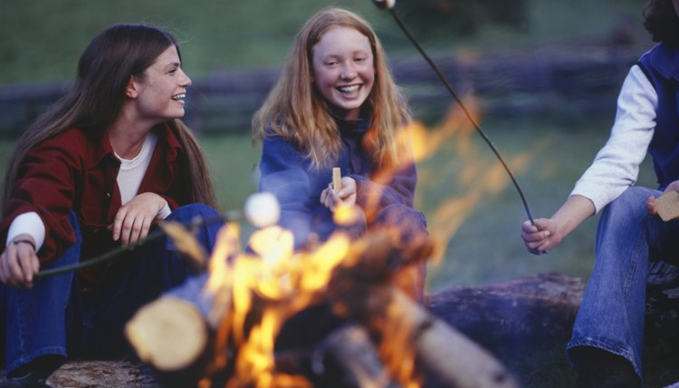 Three teenage girls (16-17) in country field roasting marshmallows over campfire