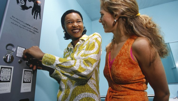 Two young women buying condoms from vending machine