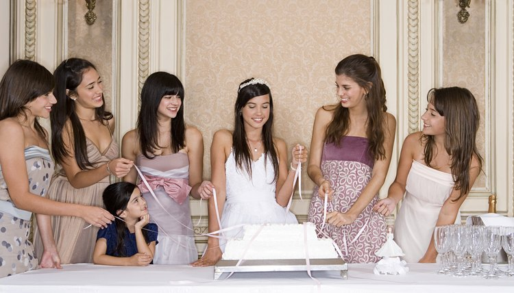 Young girls pulling ribbons from cake
