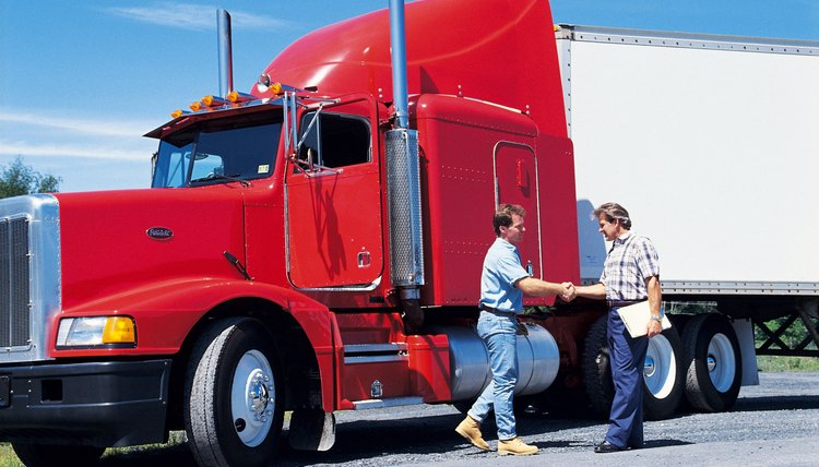 Men shaking hands beside semi