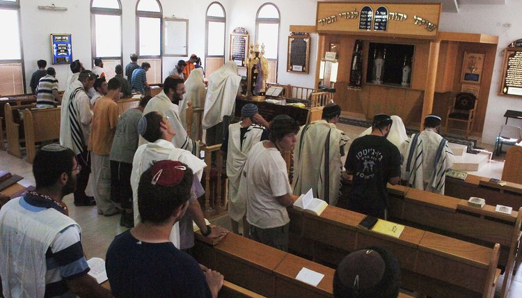 Congregation members praying in an Orthodox synagogue.