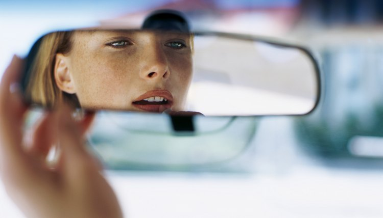 young woman looking in a rear view mirror in a car