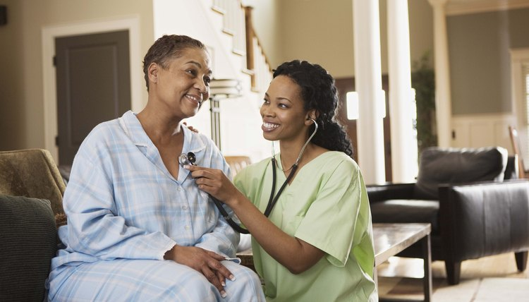 Nurse using stethoscope on patient at home