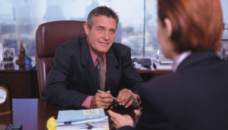 portrait of a businessman sitting at his desk and talking to a woman across