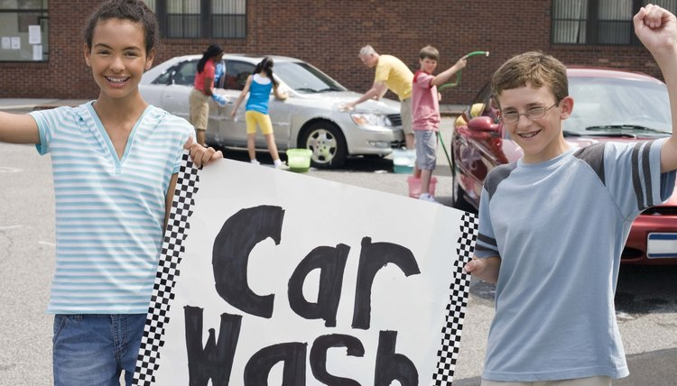 Kids holding up sign for car wash