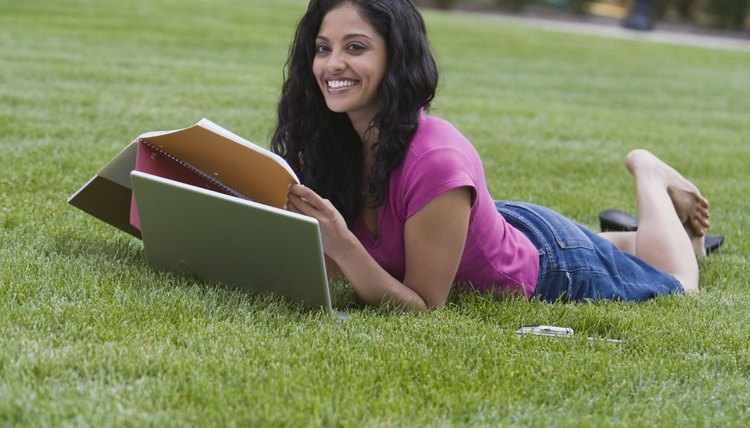 Young woman working on laptop outside on college campus lawn.